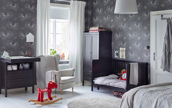 Babyzimmer in Grau, Tapete mit Blumenmuster, rotes Holzpferd, schwarze Möbel
