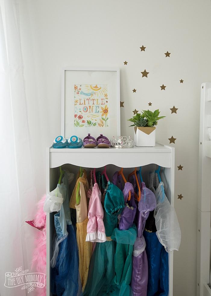 Kleiderschrank im Kinderzimmer, bunte Kinderkleider und Schuhe, grüne Pflanzen und Sternchen an der Wand