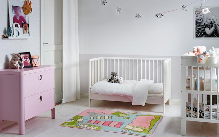 Babyzimmer Einrichtung, weißes Babybett, bunter Teppich, kleine Kuscheltiere