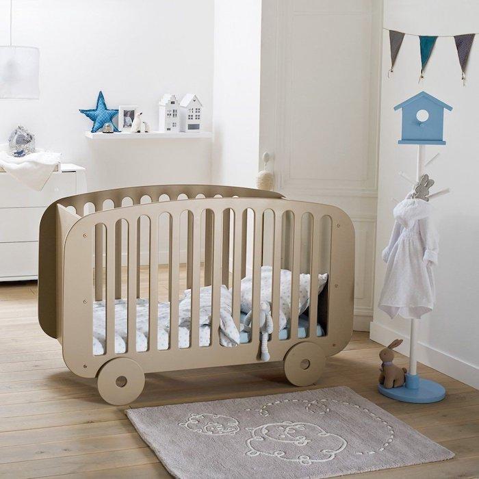 Hellblaues Babybett mit Rollen, weiße Wandfarbe, Stern Foto und kleine Häuschen auf Regal