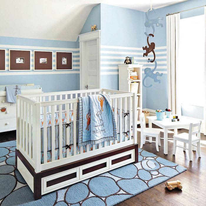 Babyzimmer in Blau, weißes Babybett, Teppich und Bettwäsche mit Affen, kleiner Tisch und Stühle