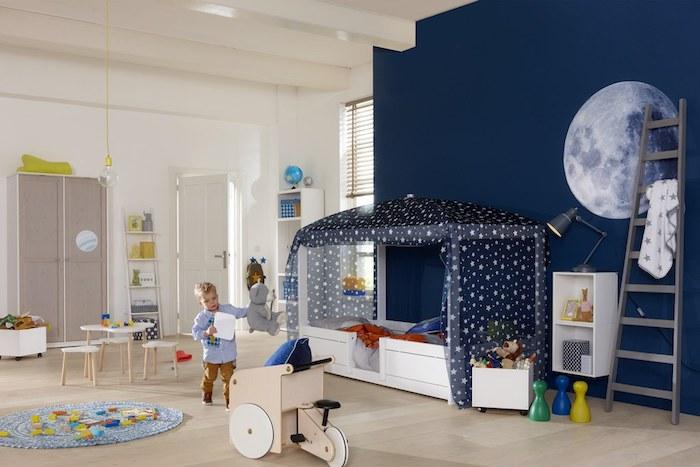 Wandfarbe Weiß, Kinderbett mit Betthimmel, hellbrauner Laminat, weiße Holzmöbel, blonder Junge