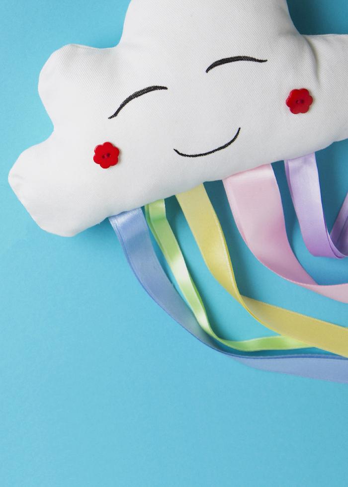 Wolke mit Gesicht, rote knöpfen für Wangen, Regenbogen aus bunten Streifen, Deko Kissen fürs Babyzimmer