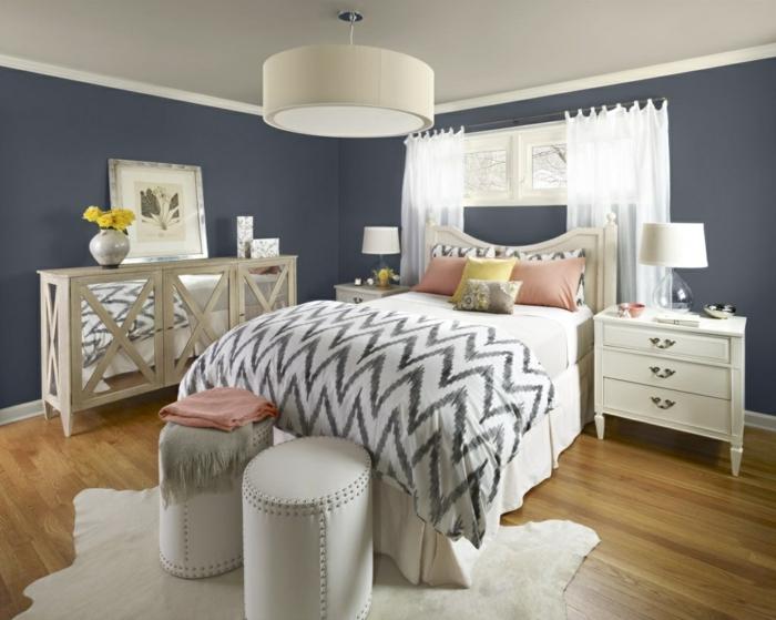 zwei weiße Hocker, Wandfarbe Hellgrau, bemusterte Bettdecke und Kissen