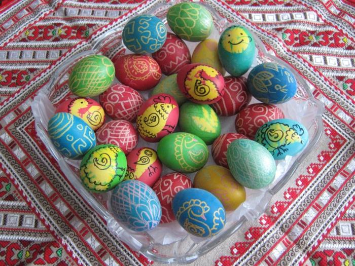 kleine Küken in gelber Farbe, Ostereierfarbe rote, grüne und blaue Eier mit Motiven