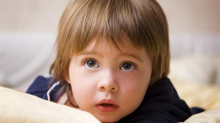 ein Kleinkind mit langem Haar, langer Pony, große braune Augen, Kinderhaarschnitt