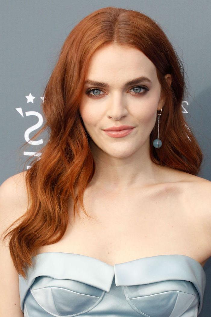 Rote Langhaarfrisur, heller Hautteint und blaue Augen, hellblaues trägerloses Satinkleid