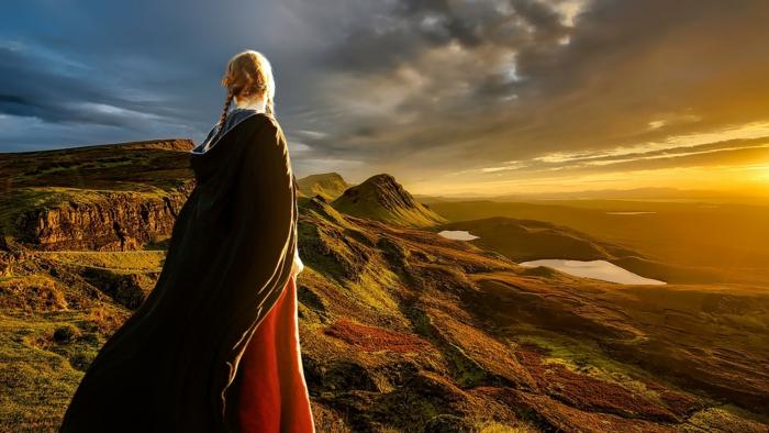 LARP - ein schönes Mädchen mit mittelalterlichem Kleid sieht in der Ferne, den Sonnenuntergang