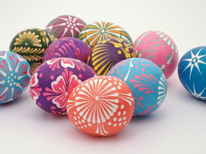 Ostereierfarbe Lila, Rosa, Orange und Blau, schöne Blumenmotive in weißer und rosa Farbe