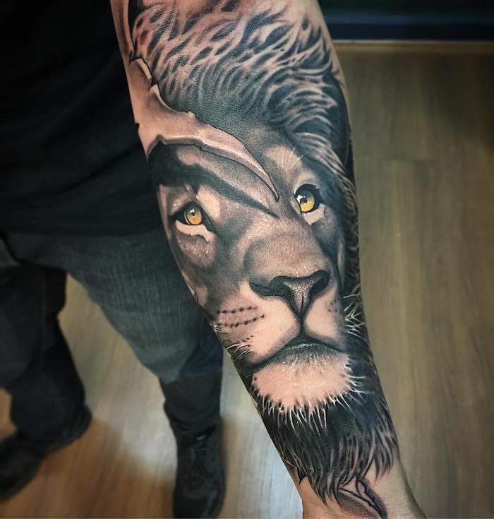 realistisches löwen tattoo am unterarm, löwe mit orangen augen, schwarz-graue 3d-tätowierung