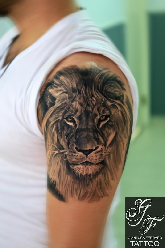 läwen tattoo am oberarm, mann mit realistischer 3d-tätowierung in schwarz und grau