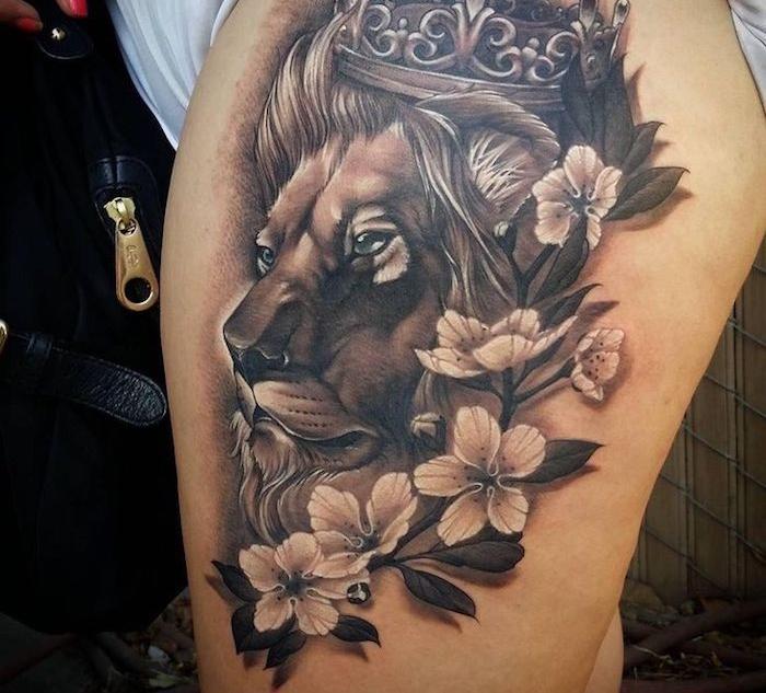 großes schwarz-graues löwenkopf tattoo am oberschenkel, weiße blüten, kirschblüten