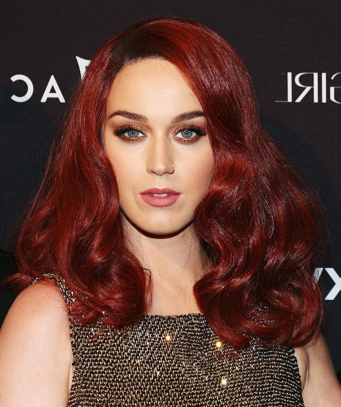 Katy Perry mit roten Haaren, Smokey Eyes und matter Lippenstift, schwarzes Kleid mit goldenen Pailletten
