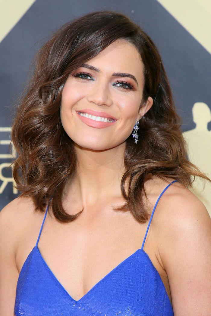Mandy Moore Langhaarfrisur, kastanienbraune Haare, blaues Abendkleid, silberne Ohrringe mit kleinen Sternchen,
