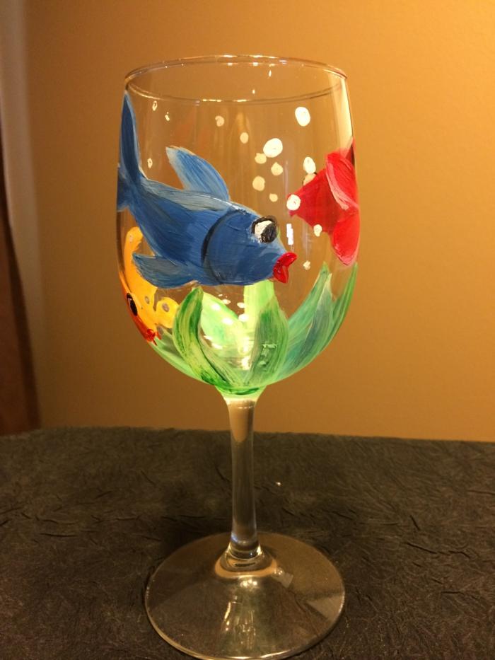 ein Glas wie ein Aquarium, ein blauer Fisch, grüne Algen und weiße Blasen