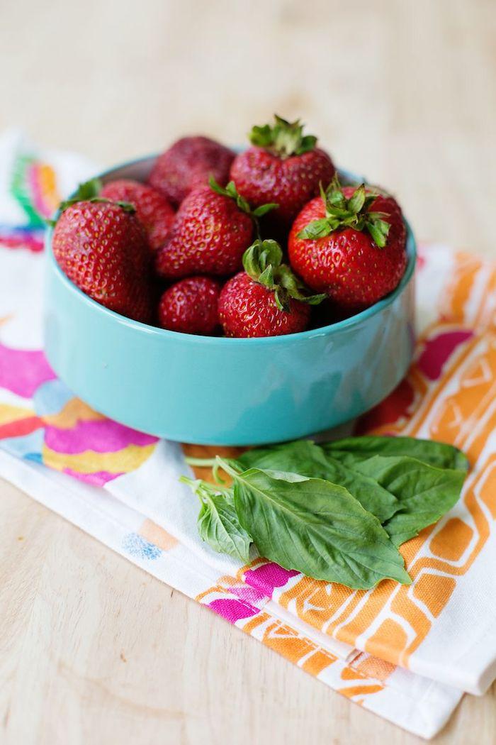 eine blaue schüssel mit vielen roten erdbeeren mit grünen blätternm eine minze mit vielen grünen blättern, ein tisch aus holz und mit einer bunten decke
