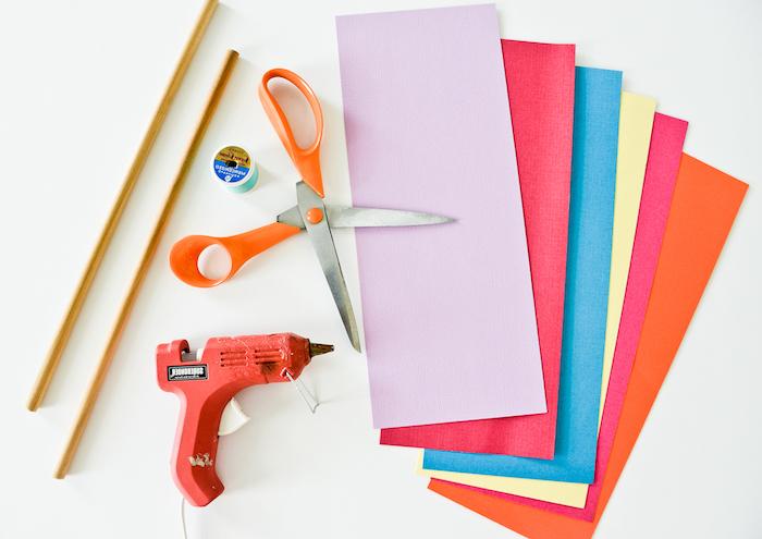 Materialien für DIY Mobile, zwei Holzstäbchen, Schere und Heißkleber, Schnur und buntes Papier