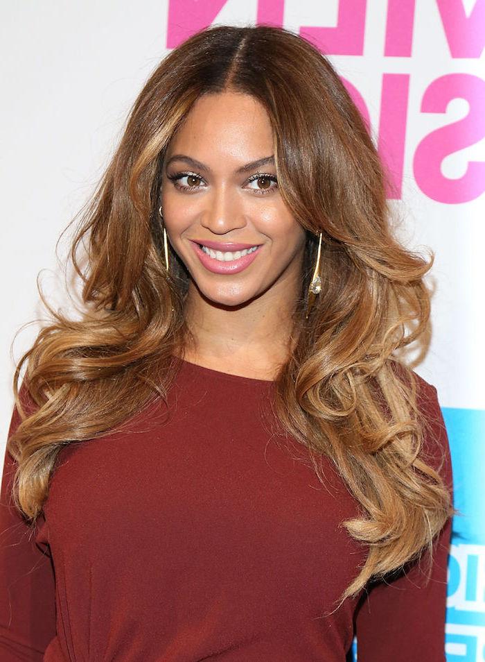 Beyonce Balayage Frisur, lange braune Haare, weinrote Bluse mit langen Ärmeln, rosa Lippenstift