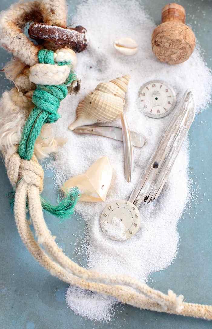 Materialien für sommerliches Hochzeitsgeschenk, Sand und Muscheln in dursichtige Weihnachtskugel füllen