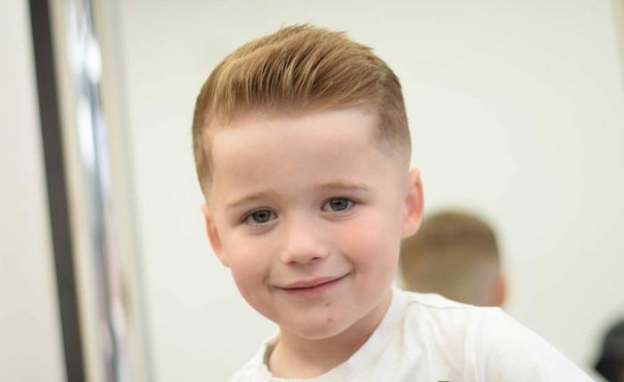 kleiner Junge mit rotem Haar, steckender Pony, entzückende Frisur Jungs