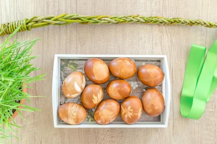 orange gefärbte Ostereier mit kleinen Blätter Technik hergestellt in schönem Körbchen