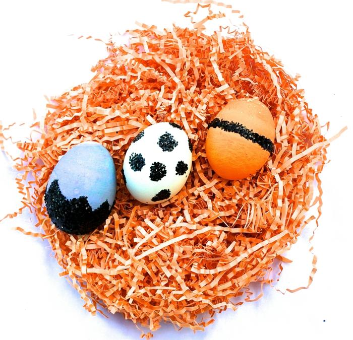 drei gefärbte Ostereier, blaue, orange, und weiße Eier mit glätzender schwarzer Farbe dekoriert