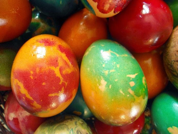 glätzende Ostereier, bunte Ostereierfarbe, ein Haufen von gefärbten Eiern
