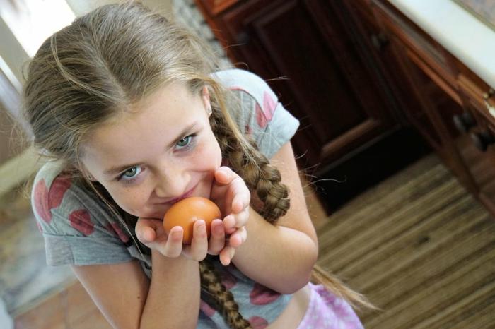 ein niedliche Mädchen trägt ein oranges Ei, Eier bemalen mit Kindern