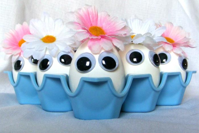 weiße Eier mit entzückenden Augen, Blumen als Mützen, Osterkörbchen