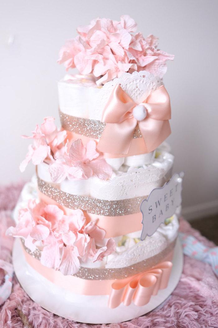 eine dreistöckige torte aus vielen weißen windeln und mit vielen pinken blumen und großen schleifen, eine windeltorte für mädchen selber basteln