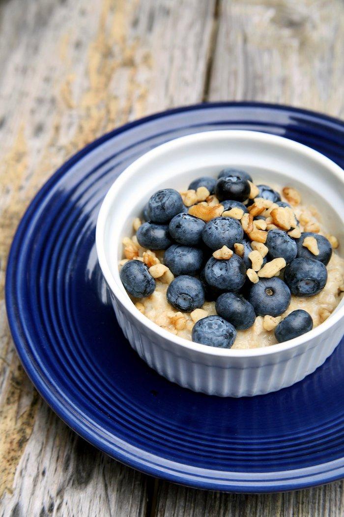 porridge rezept kalorienarm, ein dunkelblauer teller, frühstück mit quinoa und blaubeeren