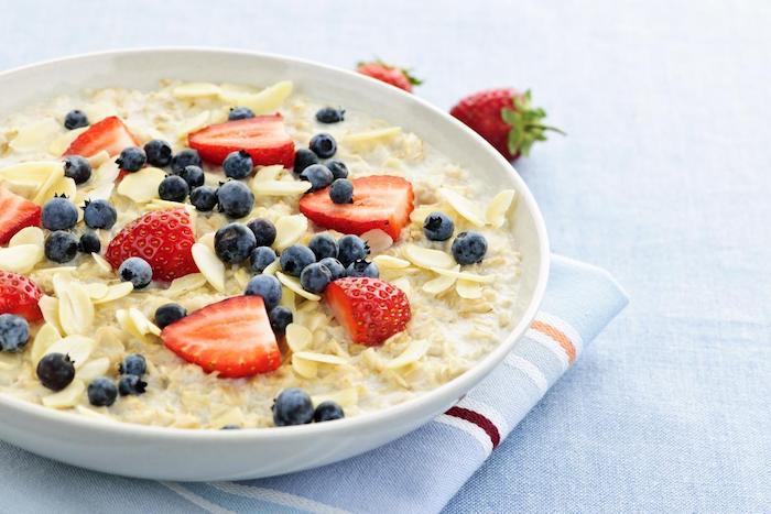 porridge rezept kalorienarm, großer weißer teller, müsli mit milch und obst, vitaminreiches essen