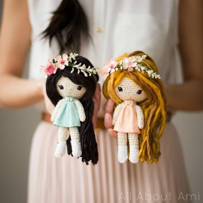Selbst gehäkelte Puppen mit langen Haaren und Blumenkränzen, die eine mit schwarzen Haaren und blauem Kleid, die andere mit blonden Haaren und rosa Kleid