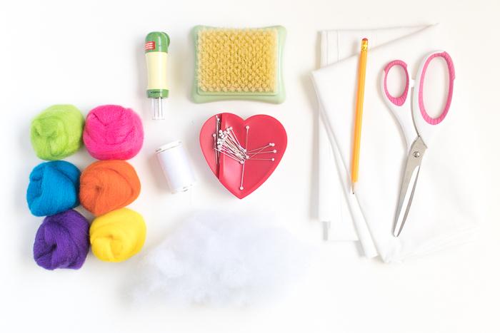 Materialien für DIY Regenbogen Kissen, Watte in unterschiedlichen Farben, weißer Stoff und Schere, Faden und Stecknadeln