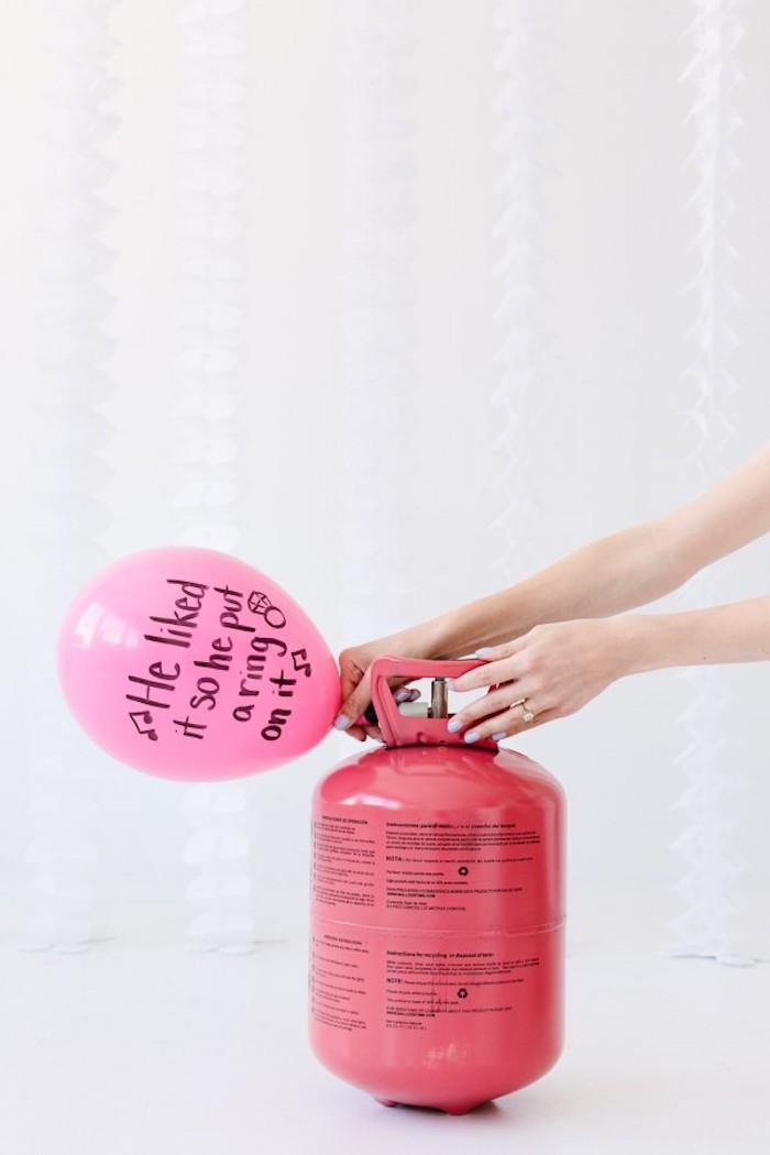 Rosa Luftballon mit Helium füllen, Botschaft mit schwarzem Permanentmarker aufschreiben
