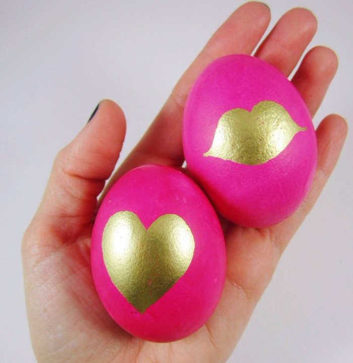rosa Eier mit goldenen Dekorationen, gefärbte Ostereier mit Herz und Kuss