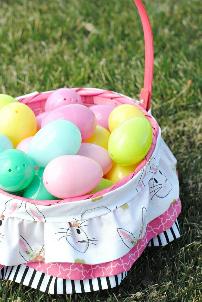 kleine bunte Eier in Körbchen mit bunten Streifen verschönert, Osterkörbchen