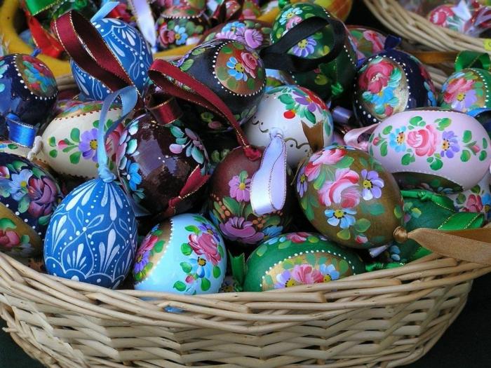 bunte gefärbte Ostereier mit Blumenmotiven in einem Rattan Köbrchen