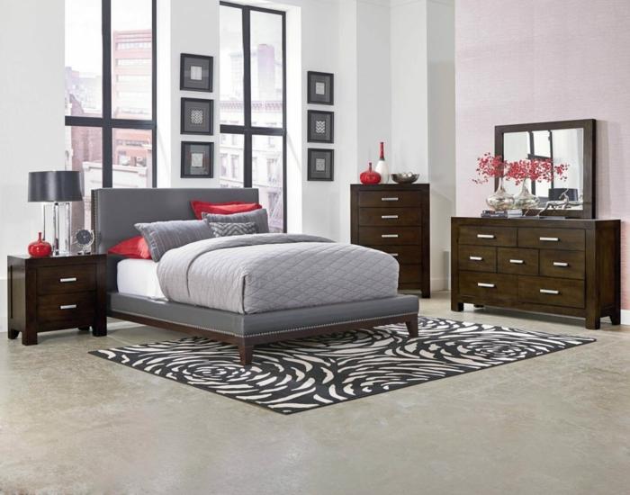 rote Akzente in einem grauen Schlafzimmer, braune Regale und zweifarbigen Teppich