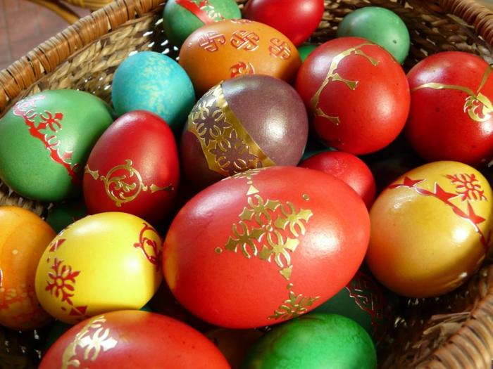 goldene Stickers für gefärbte Eier in ein großes Rattan Körbchen gelegt