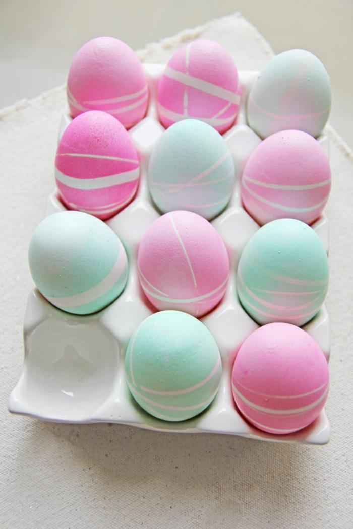 rosa und blaue Eier mit kleinen Linien von Klebeband, Ostereier anmalen