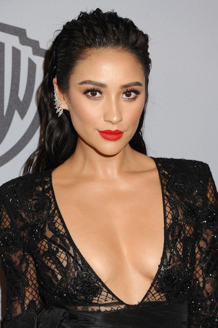 Lange schwarze Haare, olivfarbene Haut, roter Lippenstift, silberne Ohrringe mit Kristallen, schwarzes Spitzenkleid mit V-Ausschnitt