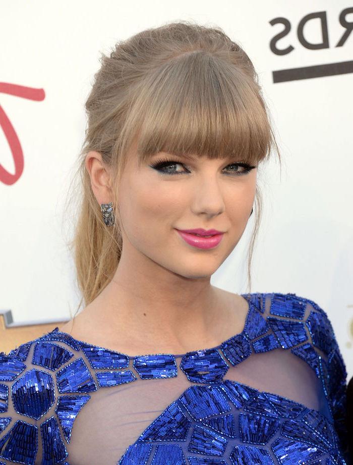 Taylor Swift Pony Frisur, dunkelblonde glatte Haare, rosa Lippenstift, dunkelblaues Kleid mit Kristallen