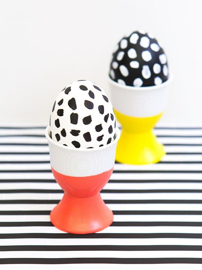 Ostereier dekorieren, zwei Eier in einem roten und einem gelben Becher