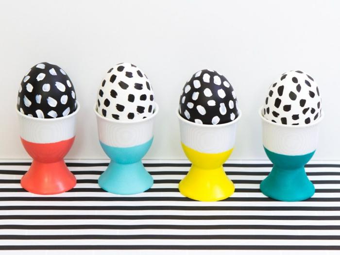 Eier anmalen, zwei blaue Becher, ein roter und ein gelber, schwarz weiße Eier