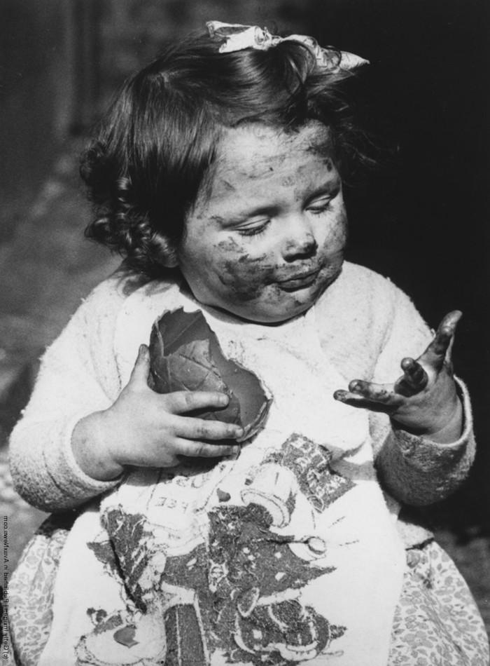 ein lustiges osterbild mit einem kleinen mädchen mit einem großen osterei aus schokolade und mit einer weißen schleife