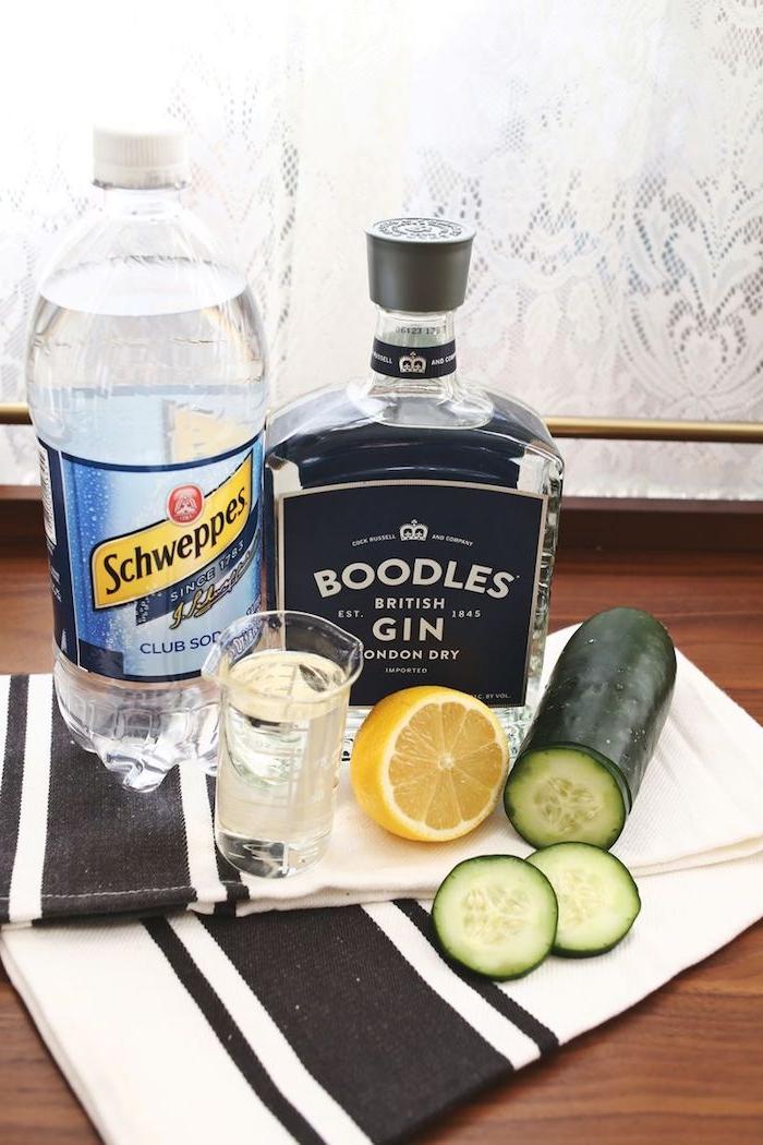 einen cocktail selber machen, eine große plastikflasche mit schweppes, eine glasflsche mit gin, ein tisch mit einer grünen gurke und mit gelben zitronen, ein tisch aus holz und fenster