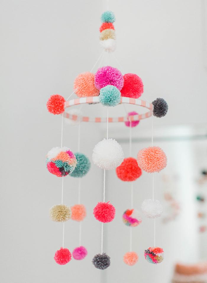 Mobile fürs Babyzimmer selber machen, bunte Pompons, Deko und Spielzeug zugleich