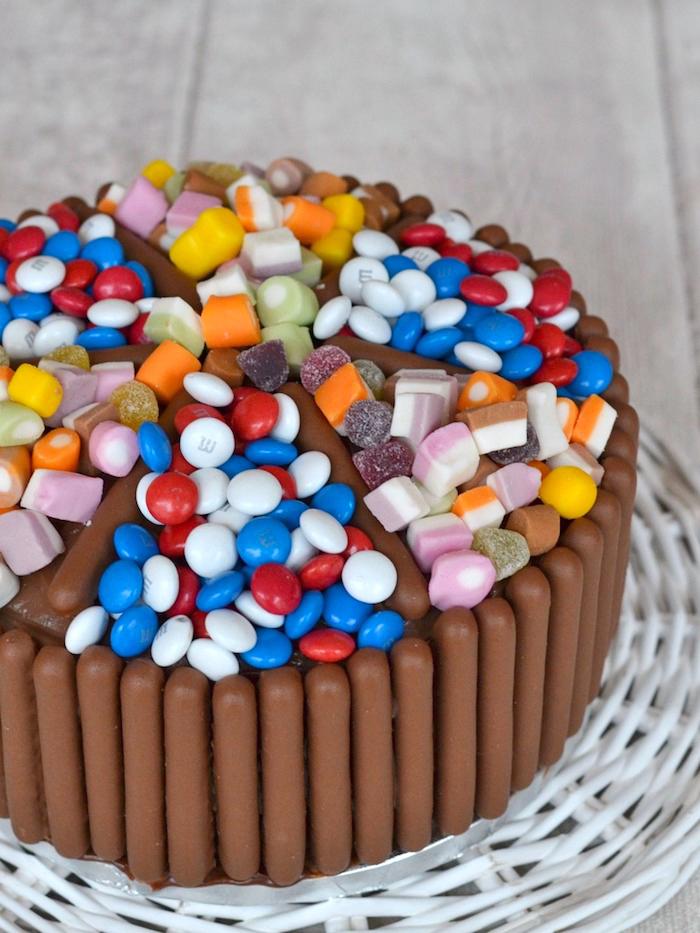 süßigkeiten kuchen dekoriert mit schokoladenriegel und bunten bonbons, geleebonbons