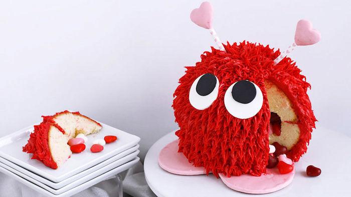 süßigkeiten torte, pinata torte gefüllt mit bonbons in form von herzen und dekoriert mit roter sahne, valentinstag geschenke